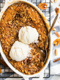 Easy Pecan Pie Cobbler with gooey filling, pecan cobbler topping, and vanilla ice cream