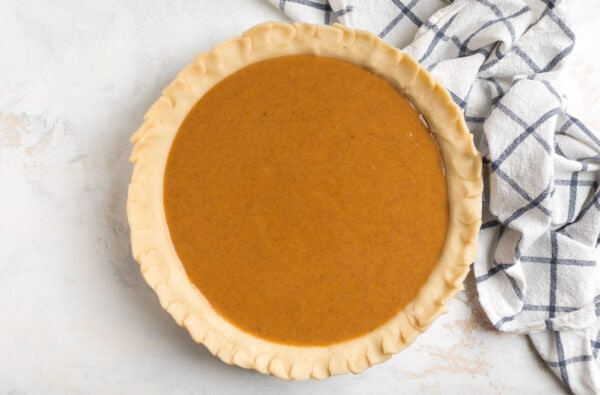 Unbaked old fashioned sweet potato pie in a pie dish
