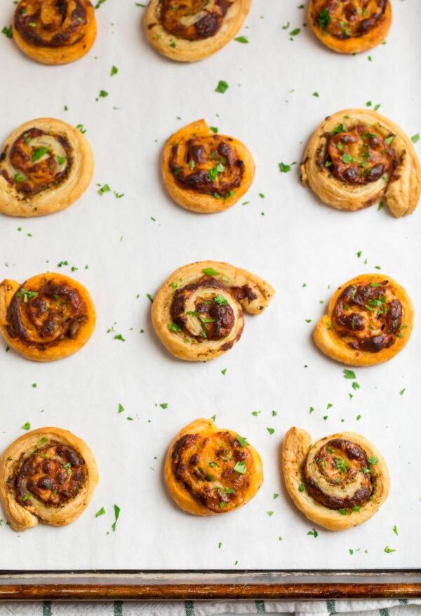Pesto pinwheels on a baking sheet with fresh herbs