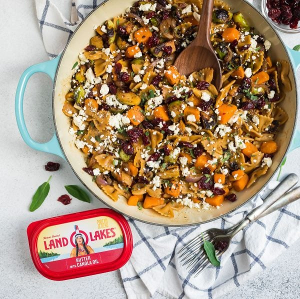 Healthy sweet potato pasta with Brussels sprouts in a pot with cranberries and cheese