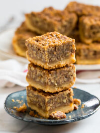A stack of pecan pie bars made with maple syrup with shortbread crust