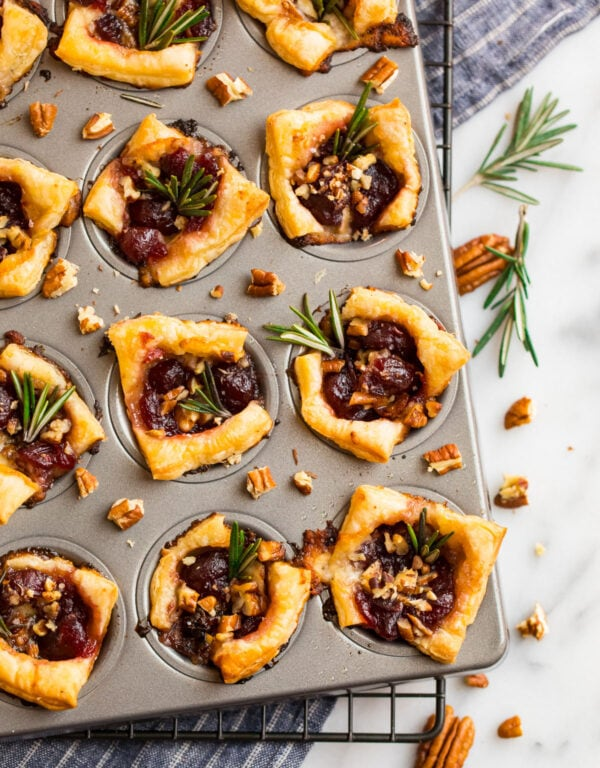 Delish cranberry brie bites in a mini muffin tin with pecans and fresh rosemary