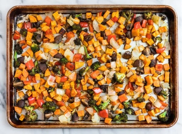 A sheet pan with roasted sweet potatoes, mushrooms, onions, red peppers, and broccoli