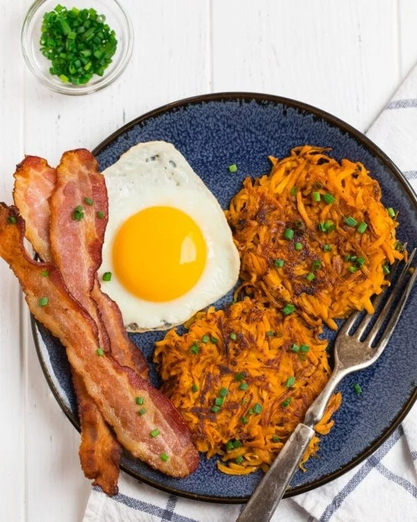 Sweet potato hash browns, eggs, and bacon served on a plate