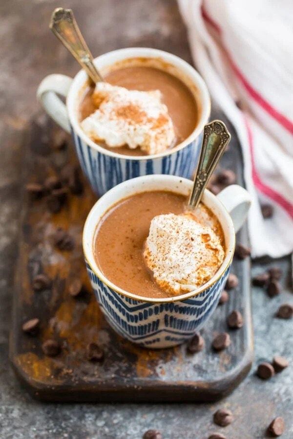 Healthy hot chocolate with almond milk served in mugs with whipped cream