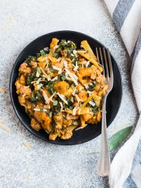 A plate of creamy butternut squash pasta with chicken sausage, kale, and Parmesan topped with sage