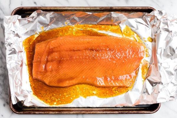 A side of salmon on a baking sheet coated in a sweet, sticky teriyaki glaze