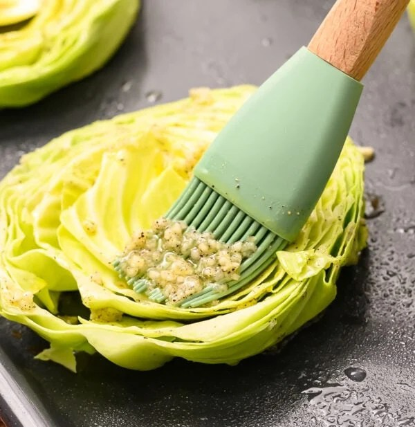 A cabbage steak being brushed with an olive oil, garlic, salt, and pepper mixture