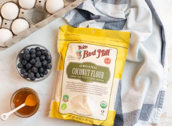 A bag of coconut flour, blueberries, eggs, and honey for making healthy muffins