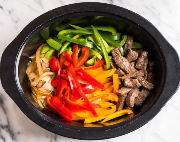 A slow cooker with beef, peppers, and onions for making pepper steak
