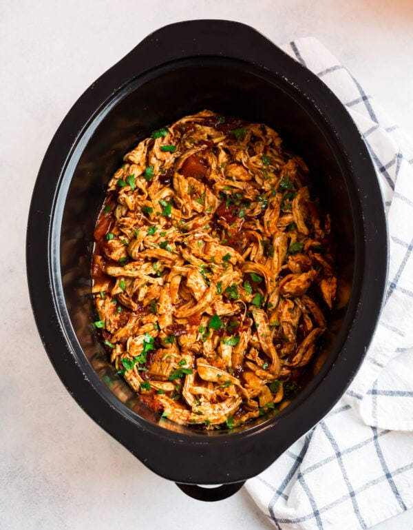 A slow cooker full of delicious shredded meat for using on tons of recipes