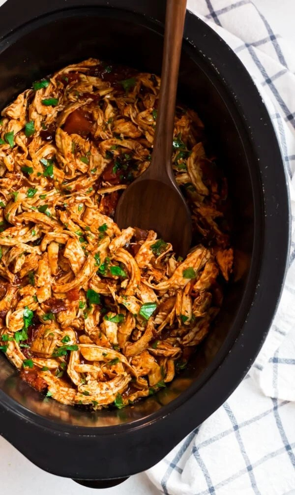 A wooden spoon in a slow cooker full of shredded meat with tons of flavor