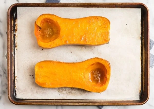 Two halves of a vegetable on a sheet pan for roasting