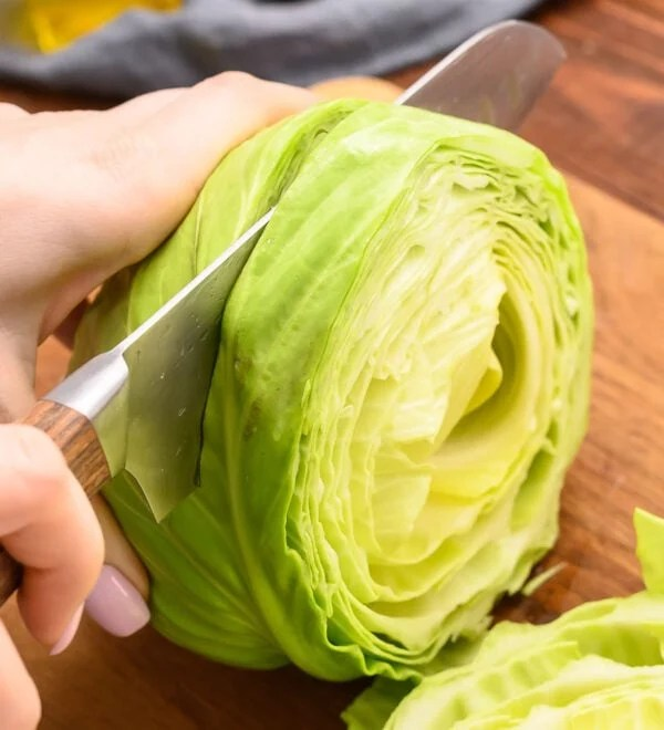 A knife slicing through a head of cabbage