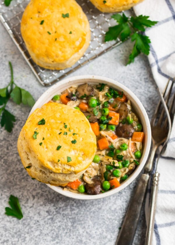 Healthy Crockpot Chicken Pot Pie Filling in a bowl topped with biscuits