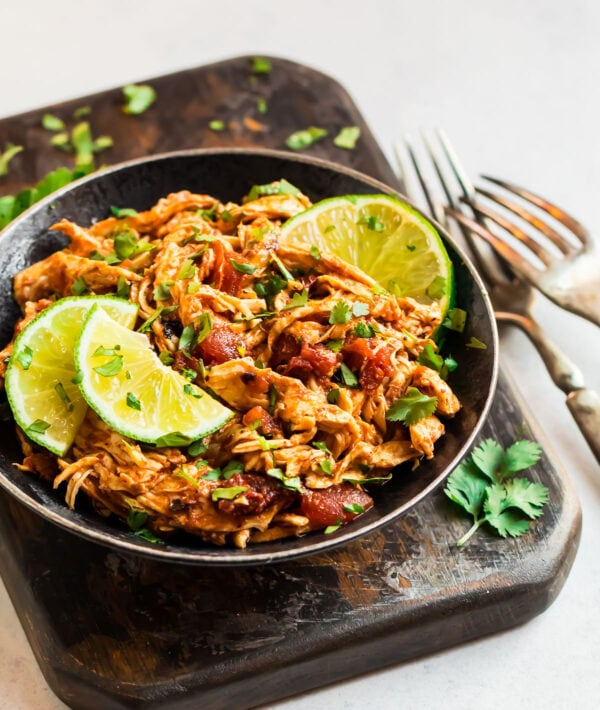 Slow cooker Mexican chicken thighs or breasts served in a bowl with lime wedges