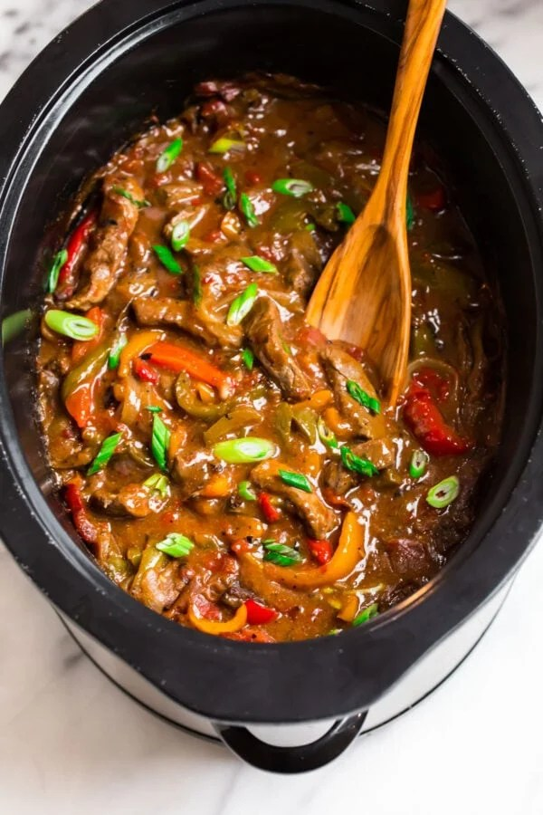 A slow cooker with beef and vegetables in a sticky Asian sauce