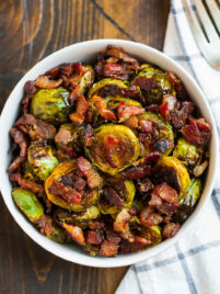 a bowl with roasted maple bacon brussels sprouts with bacon pieces on top