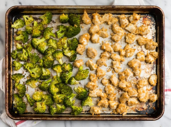 Broccoli and chicken pieces on a sheet pan for making one of the best healthy chicken breast recipes