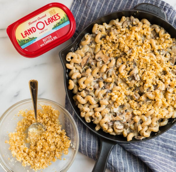 The best mac and cheese in a skillet, a tub of butter, and a bowl of Panko and Parmesan