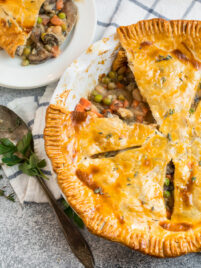 A vegetarian pot pie made with white beans and mushrooms and vegetables in a white pie dish