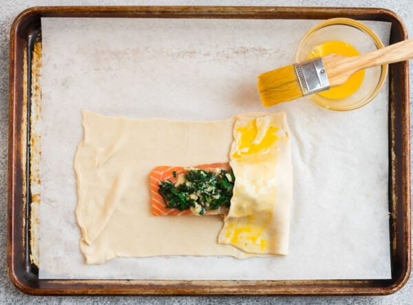 A parchment-lined baking sheet with a fillet of fish wrapped in puff pastry
