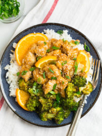 Healthy orange chicken with rice and broccoli on a blue plate