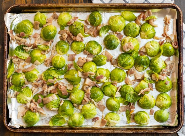 Brussels sprouts and bacon arranged in an even layer on a baking sheet