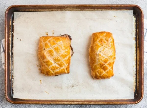 Two fish filets wrapped in golden puff pastry on a baking sheet