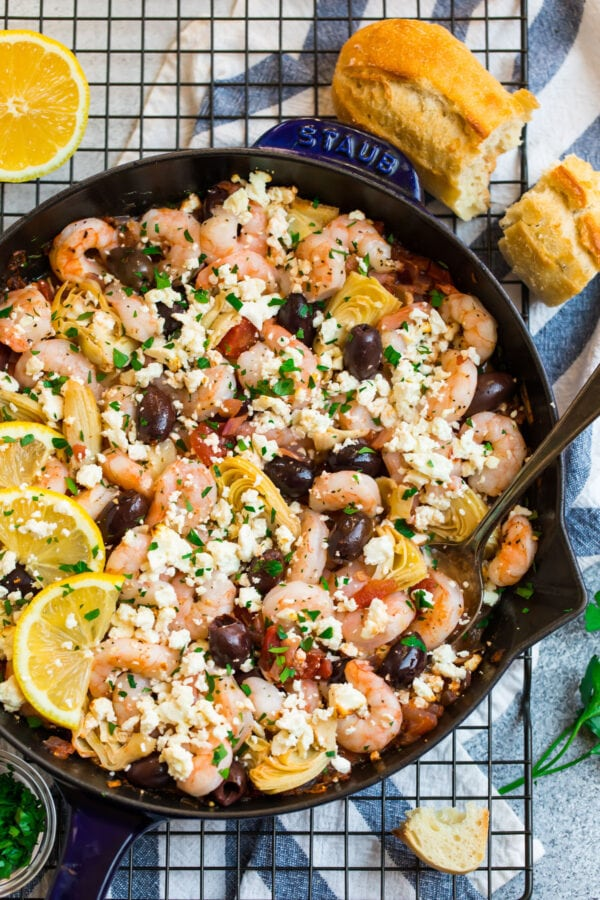 Mediterranean garlic shrimp recipe in a skillet with a side of bread