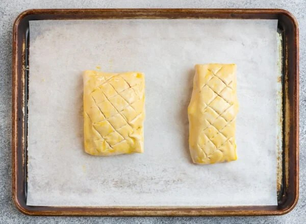 Two unbaked pieces of salmon Wellington on a baking sheet