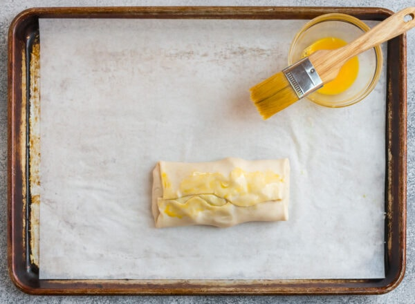 Puff pastry wrapped around a salmon fillet on a parchment-lined baking sheet