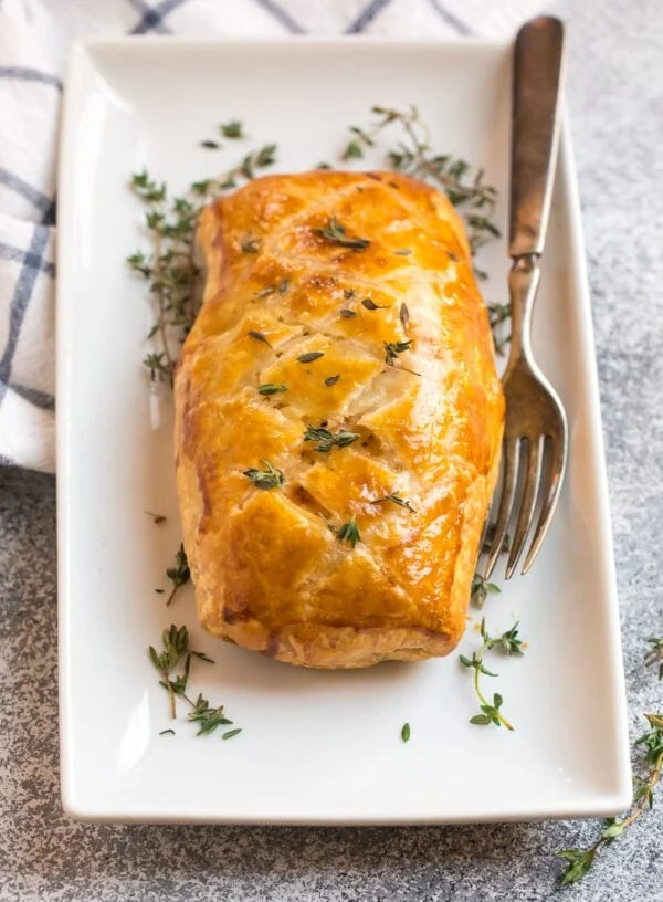 A white plate with delicious fish wrapped in buttery puff pastry