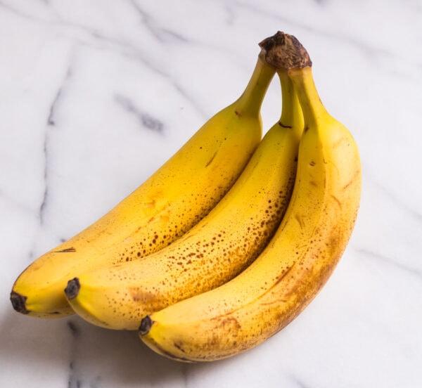 Three ripe bananas on a counter