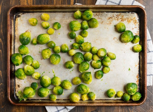 A baking sheet with parboiled Brussels sprouts