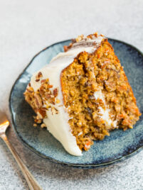 A blue plate with a slice of moist gluten free carrot cake with almond flour topped with cream cheese frosting