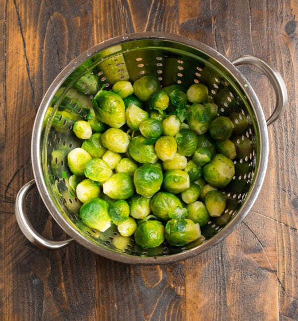 A colander with green, parboiled vegetables