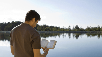 man reading bible near lake