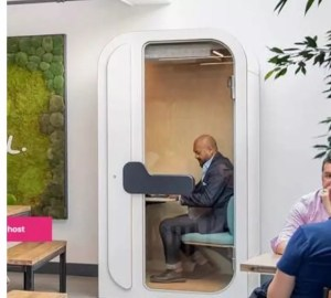 Man works from an individual work pod - remote working co-working productivity