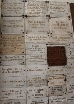 """Plaques thanking Saint Clement for various things. At bottom right one thanks him for """"the homecoming of my sons"""" in 1945"""