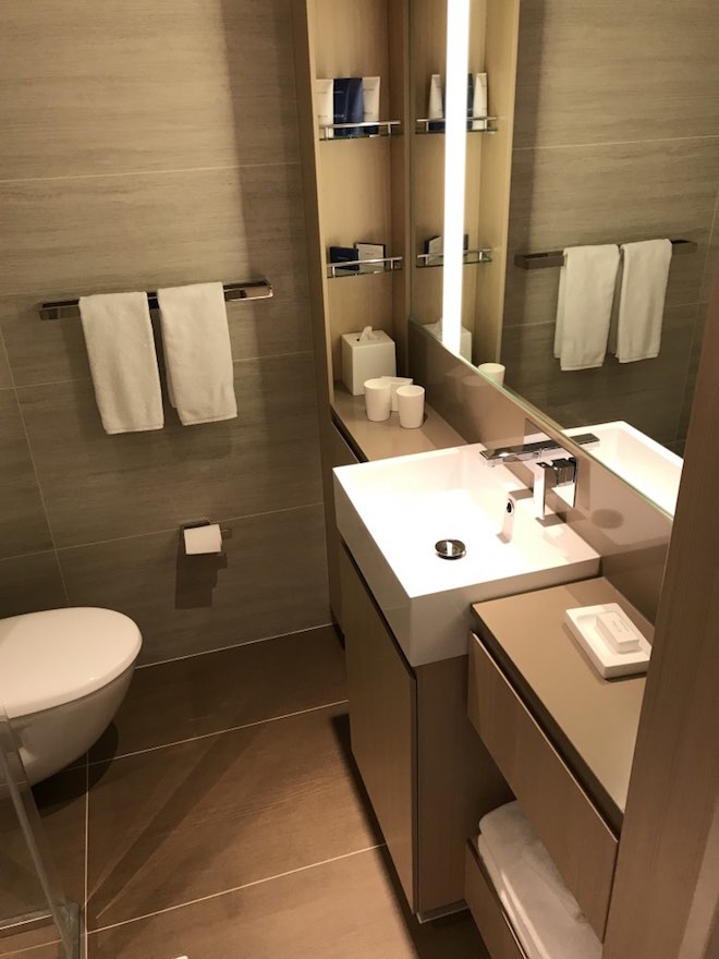 Large bathroom with square sink and deluxe toiletries.