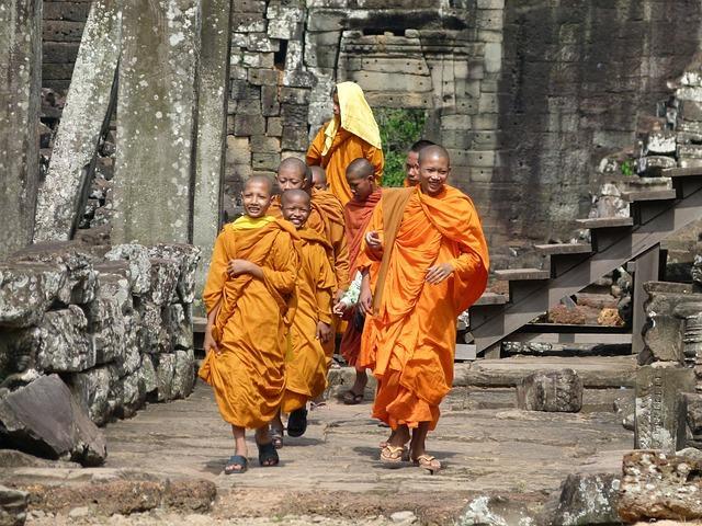 Moenche laufen durch die Tempelanlagen in Kambodscha.