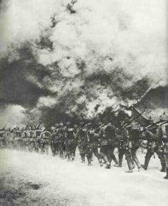 Deutsche Infanterie marschiert durch brennendes Dorf