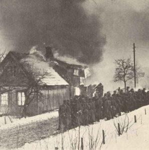Deutsche Truppen in einem brennenden norwegischen Dorf.