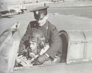 einem polnischer Piloten durch einen Unteroffizier der polnischen Luftwaffe in sein Flugzeug geholfen