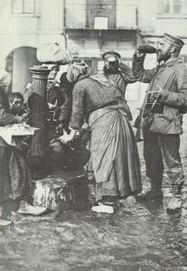 Deutsche Soldaten am Brunnen einer serbischen Stadt.