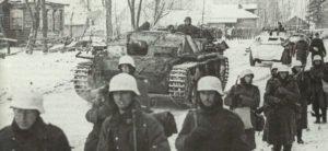 Deutsche Panzerfahrzeuge und Infanteristen auf dem Marsch in eisiger Kälte