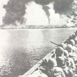 Japanische Soldaten betrachten von ihren Landungsfahrzeugen aus das brennende Manila.