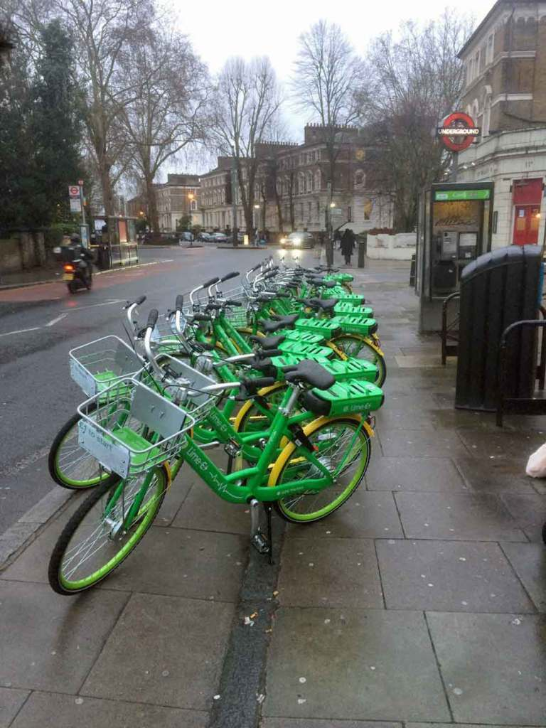 A row of LimBikes on a pavement, disorderly organised