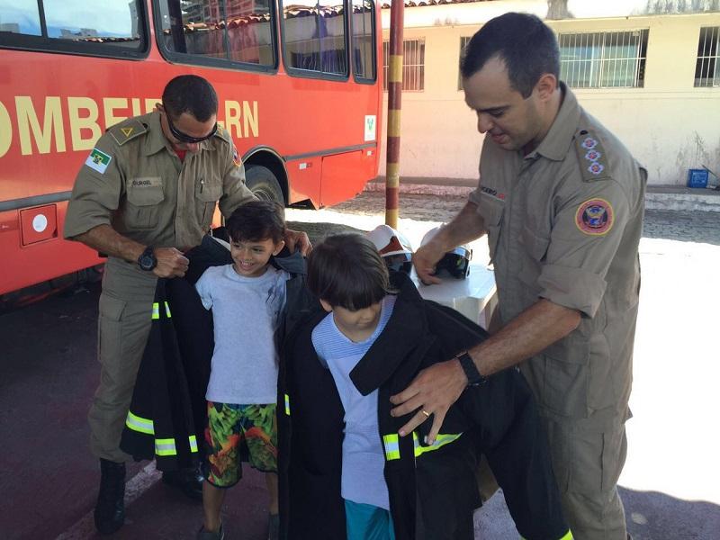 Crianças vestem a roupa dos bombeiros